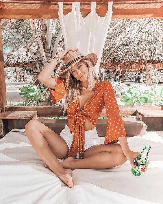 white denim shorts, a rust polka dot tie blouse with bell sleeves and a straw hat