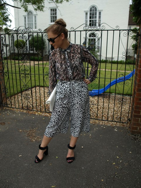 With animal printed blouse, white clutch and black shoes