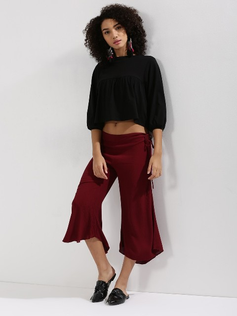 With black crop shirt and black leather flat mules