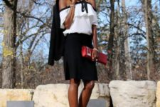 With black skirt, red clutch, ankle strap shoes and blazer