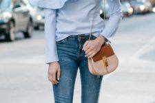 With distressed jeans and brown and beige bag