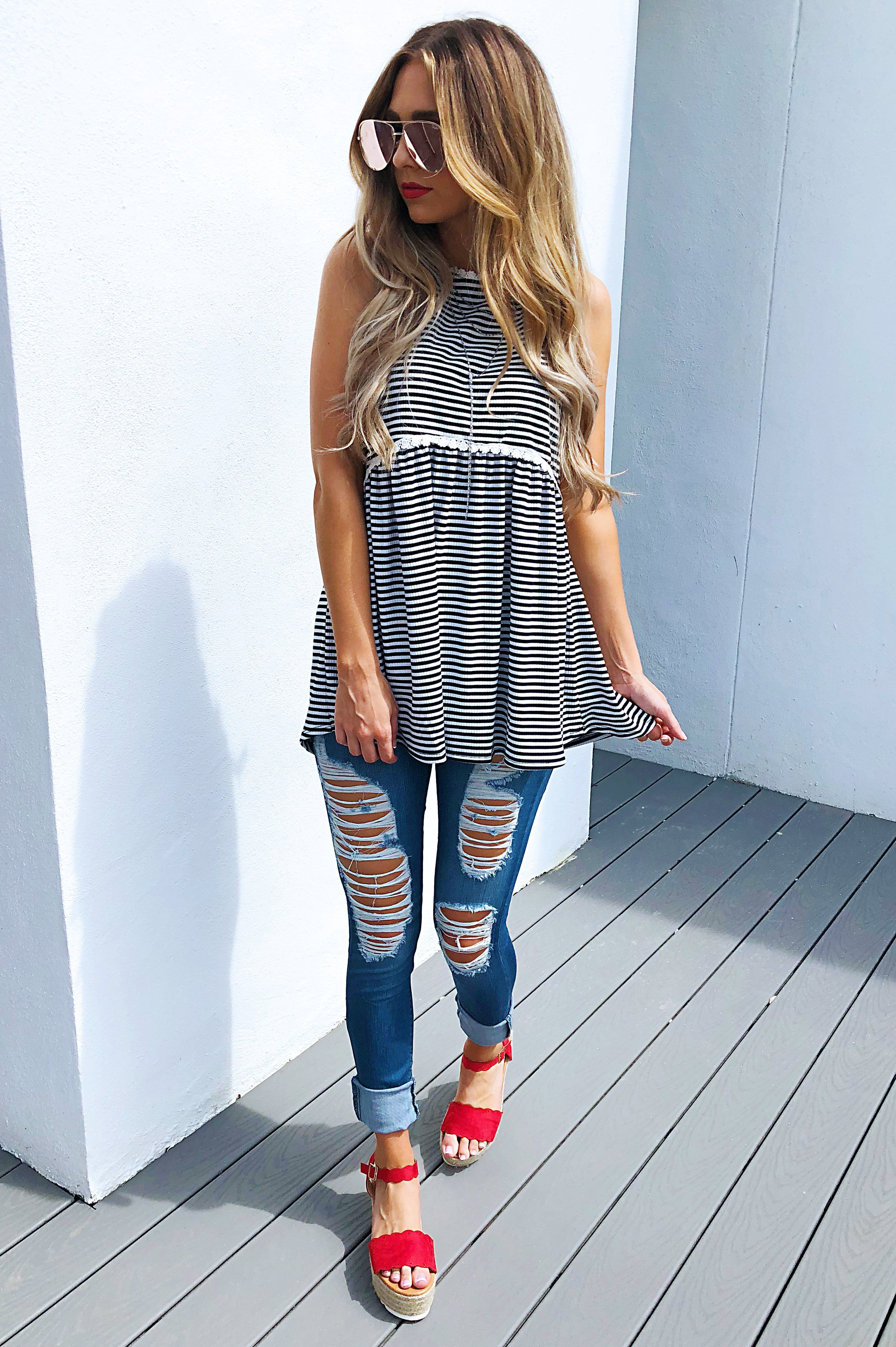 With distressed jeans and red platform sandals