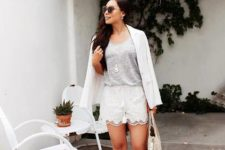 With gray top, white blazer, straw bag and flat sandals