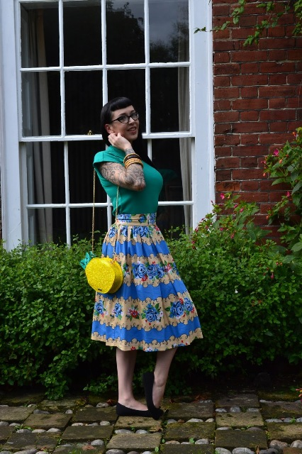 With green shirt, printed midi skirt and black flats