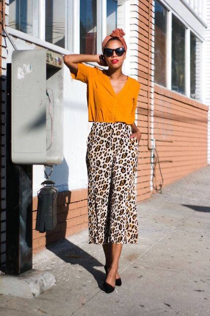 With orange shirt, black flats and sunglasses