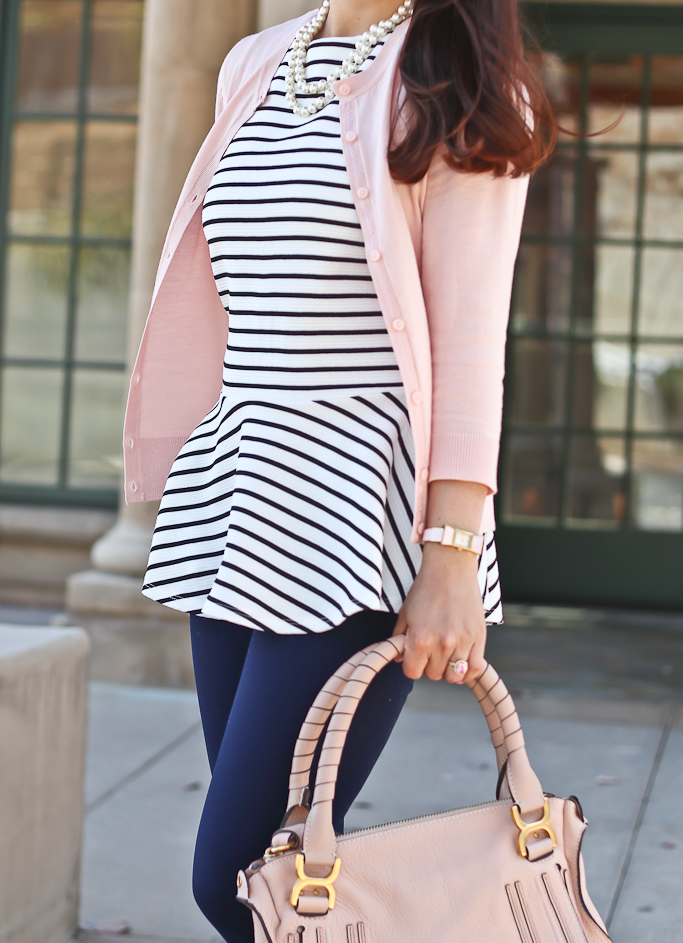 With pale pink jacket, jeans and pale pink bag
