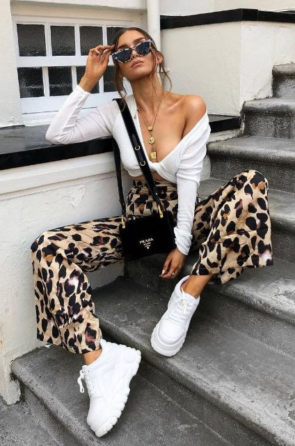 With white crop top, black small bag and white platform sneakers