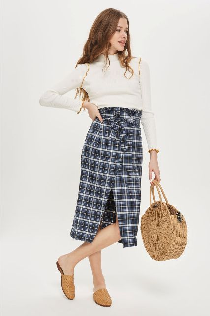 With white shirt, straw rounded bag and flat mules