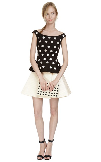 With white skirt, polka dot clutch and ankle strap high heels