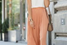 With white top, brown mini bag and black sandals