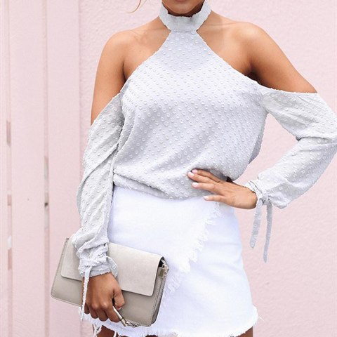 With white wrapped skirt and gray clutch