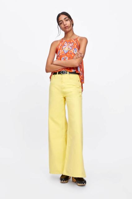 With yellow flare trousers, black belt and shoes