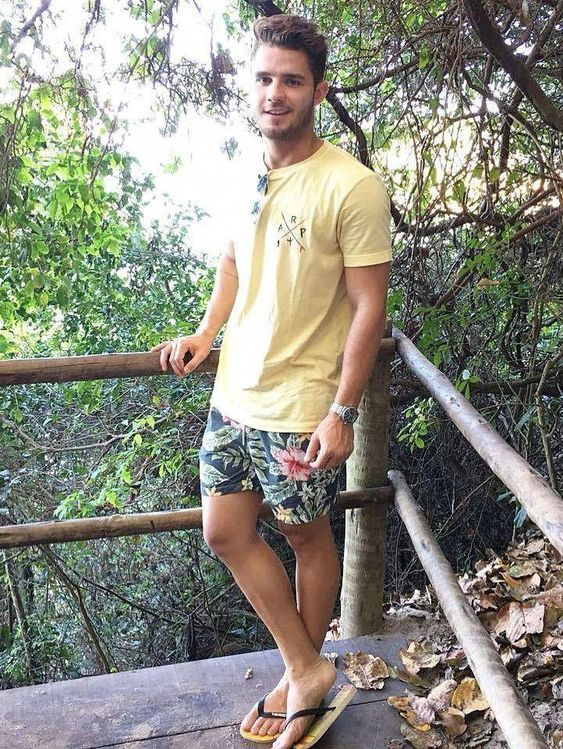 a simple tropical look with a yellow t shirt, bright florla swim trunks and flipflops is beach ready