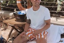 a white tee and orange and white vertical stripe trunks for a cheerful and bright beach look