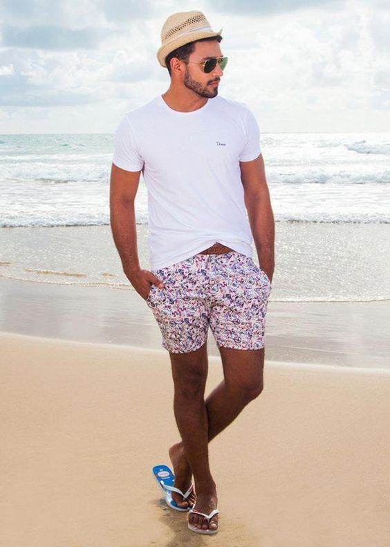 a white tee, bright floral swim trunks, flipflops and a straw hat for a comfy beach outfit