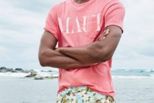 colorful blue floral print swim trunks paired with a pink t-shirt for a fun and bold look
