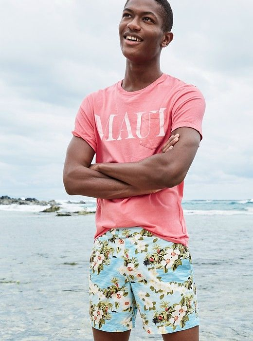 colorful blue floral print swim trunks paired with a pink t shirt for a fun and bold look