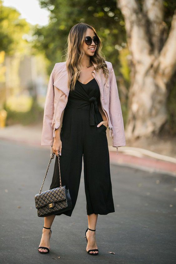 a black culotte jumpsuit with wideleg pants, black heels, a pink leather jacket and a black bag