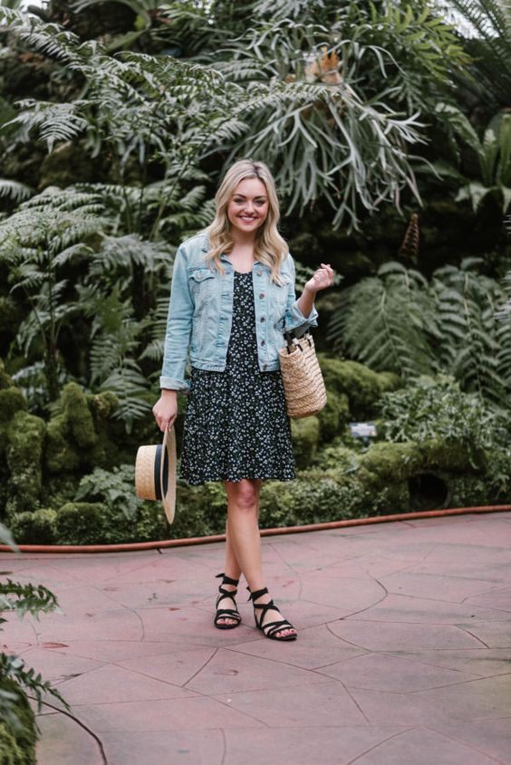 a black floral knee dress, a blue denim jacket, black lace up sandals, a straw bag and hat