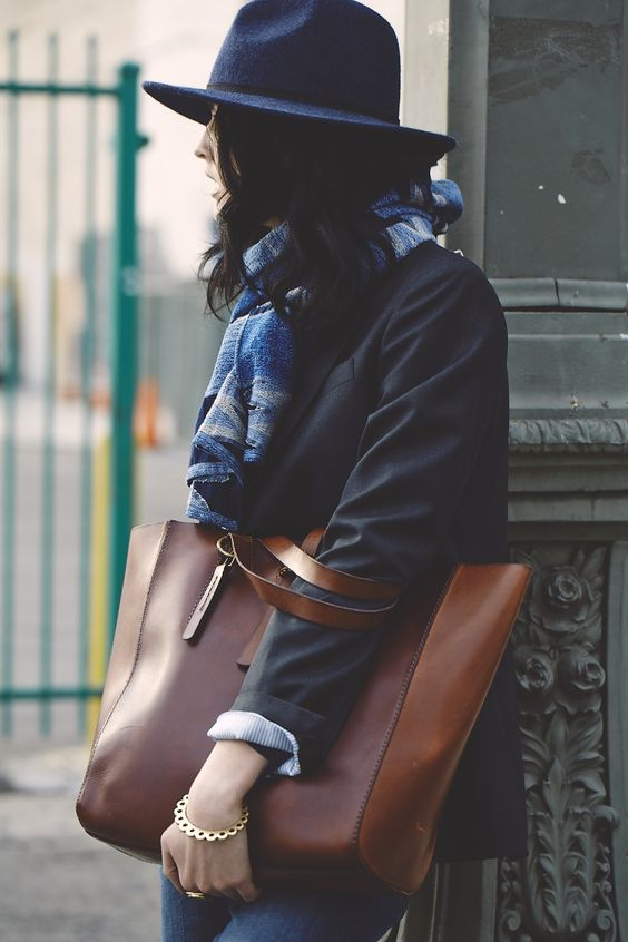 a brown leather mid-sized tote is a chic basic option to carry your laptop and much other stuff in