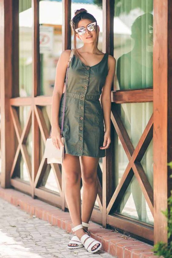 a green mini dress with brown buttons and thick straps plus white strappy shoes and a matching bag