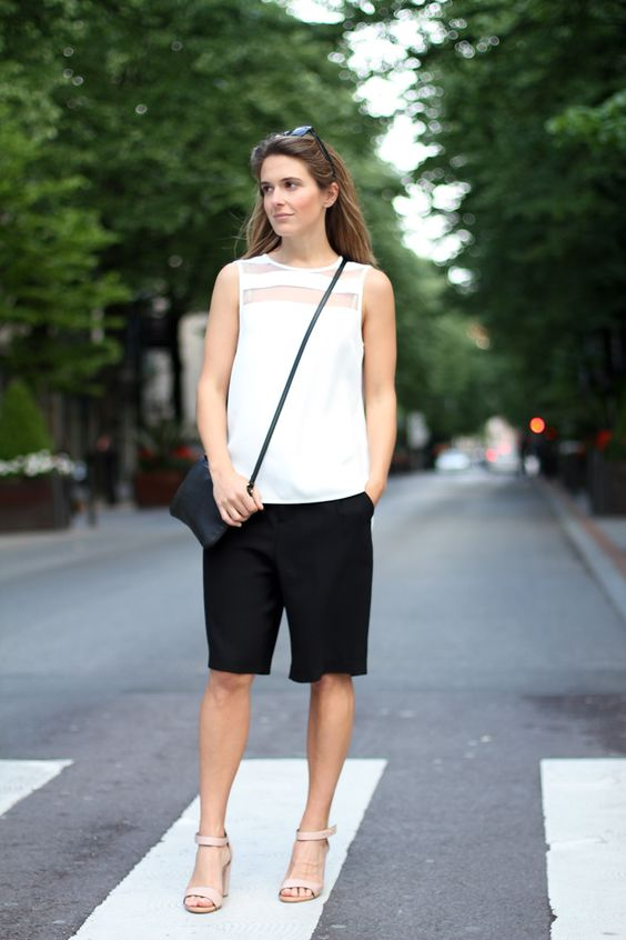 a minimalist office look with a sleeveless white top, long black shorts, neutral shoes and a navy cross body bag