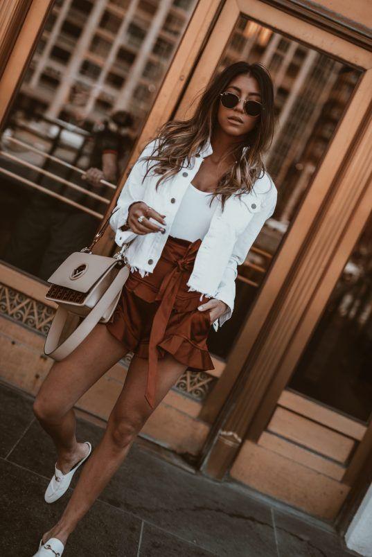 a white denim jacket, a white tee, cognac ruffle shorts, white mules and a blush bag