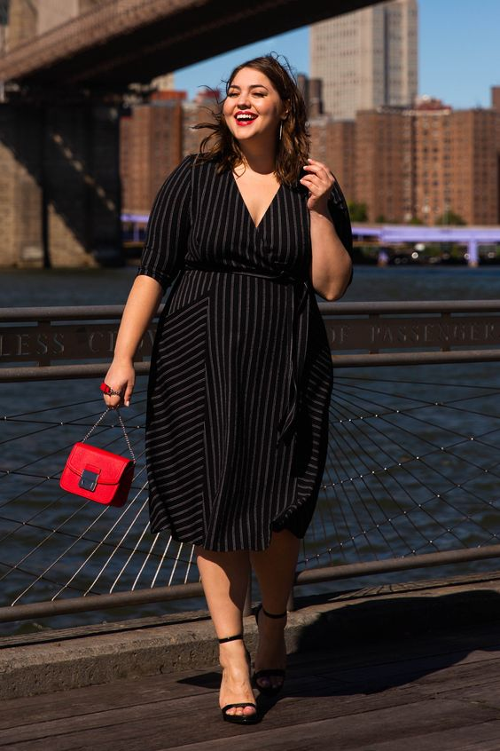 a black wrap midi dress with thin stripes, black heels and a small red bag for a bold look