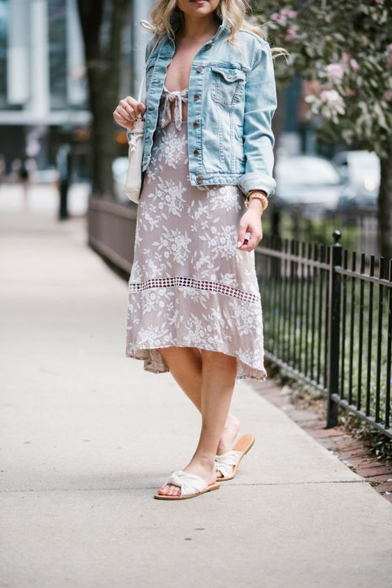 a blush floral midi dress with a blue denim jacket, white slippers and a matching bag