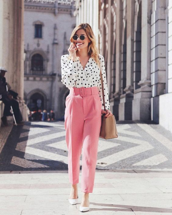 a bright look with a white and black polka dot shirt, high waisted pink pants, white shoes and a camel bag