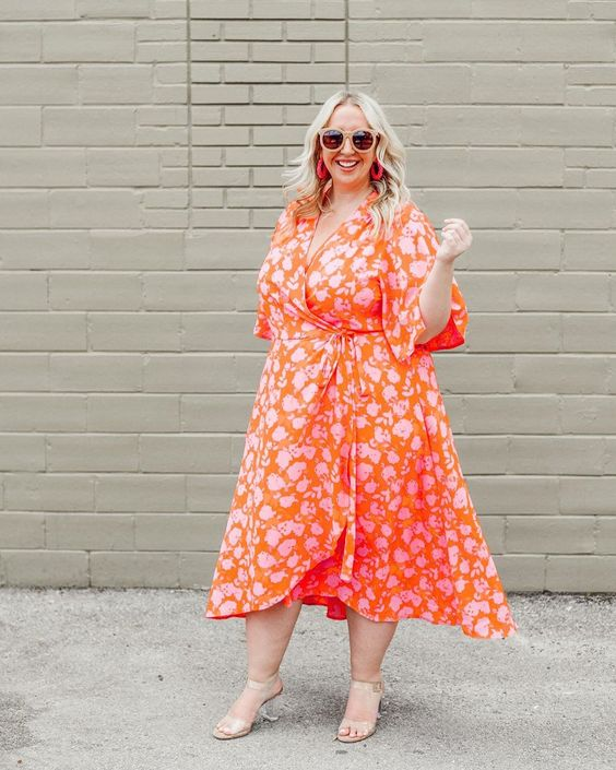 a bright orange wrap midi dress with a floral print and an asymmetrical skirt and sheer heels