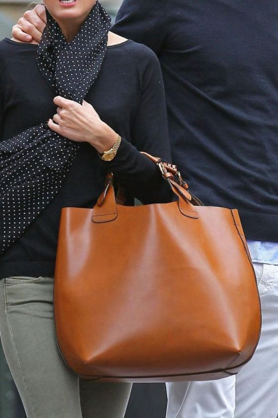 a large amber leather catch all tote with short yet comfortable handles is a timeless accessory to rock