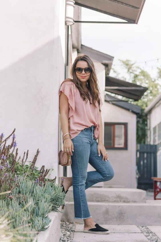 a pink loose top, blue raw hem flare jeans, black espadrilles and a brown bag