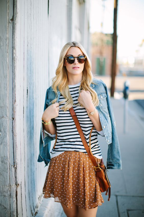 a mixed print look with a striped tee, a polka dot ocher skirt, a brown bag and a blue denim jacket