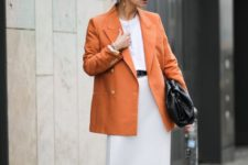 04 whimsy black shoes, a white tee, a white midi skirt, an orange oversized blazer and a large black clutch