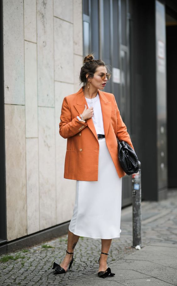 whimsy black shoes, a white tee, a white midi skirt, an orange oversized blazer and a large black clutch