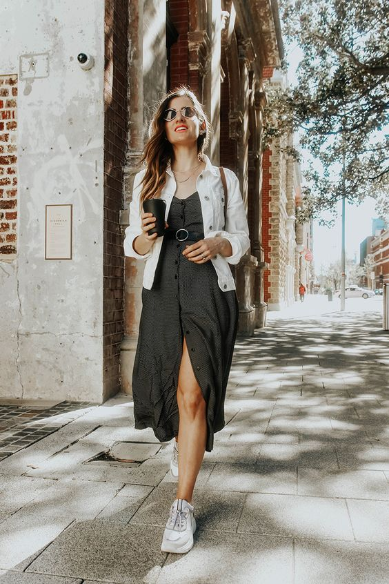 a graphite grey button midi dress with a sash, a white denim jacket, white sneakers and a brown bag