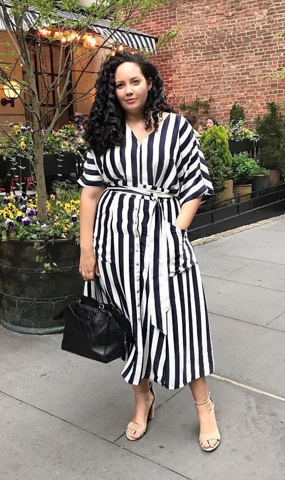 a striped black and white midi dress, a black bag and nude heels are a perfect look for summer