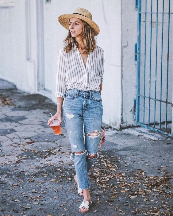a striped shirt, blue ripped jeans, white sliders, a straw hat for a summer to fall look