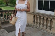 05 a white fitting midi dress with ruffles and black buttons, espadrilles and a straw bag for a vacation look