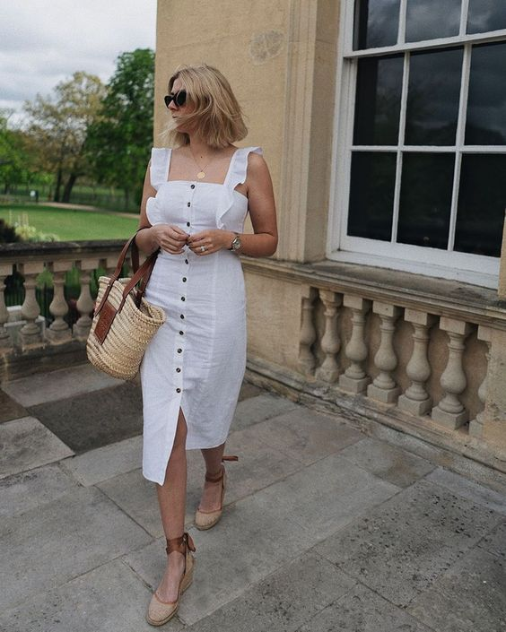 a white fitting midi dress with ruffles and black buttons, espadrilles and a straw bag for a vacation look