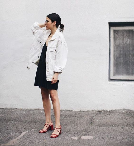 a black mini dress, an oversized white denim jacket, red strappy shoes