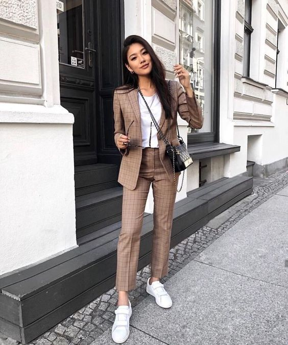 a stylish brown plaid suit, a white tee and white sneakers for a casual yet formal look
