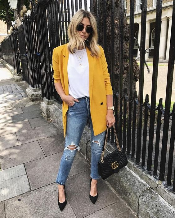 blue ripped jeans, a basic white tee, black shoes and a black bag plus a sunny yellow oversized blazer