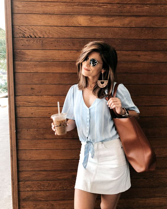 a blue tied shirt, a white denim mini skirt, a brown bag and statement earrings