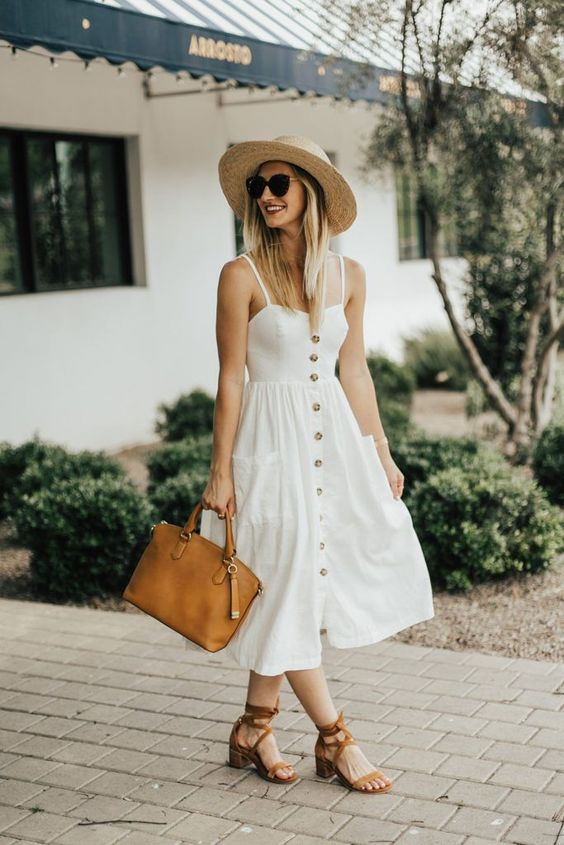 a comfortable white A-line midi dress on a row of buttons, brown strappy shoes, a straw hat and a brown bag