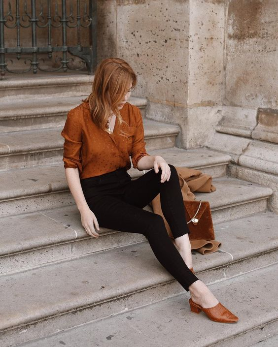 a gorgeous retro-inspired look with black cropped skinnies, a rust-colored shirt and matching mules plus a bag