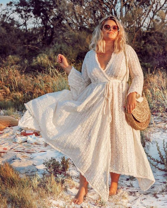 a neutral boho lace midi wrap dress with an asymmetrical skirt and long sleeves and a woven bag for a holiday