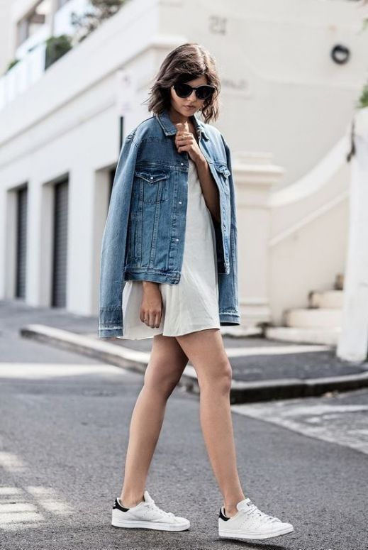 a white mini dress, white sneakers and an oversized denim jacket for a minimal look