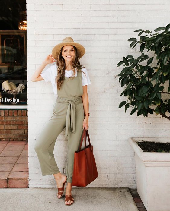 a white tee, a green overall, brown leather sandals and a matching tote bag plus a straw hat